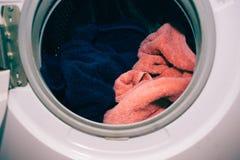 洗衣机门,干净的五颜六色的衣裳,蓝色和桃红色毛巾 免版税库存照片
