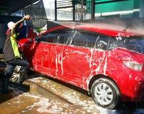 洗车的一台人喷洒的压力洗衣机在汽车保养商店在曼谷泰国 免版税库存照片