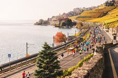 洛桑地区,小行政区沃州,瑞士2016年10月30日:在审阅拉沃葡萄园梯田葡萄园的洛桑马拉松的赛跑者 库存图片