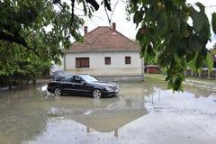 洪水,在被充斥的房子前面的汽车的后果 库存照片