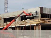 活动空中大厦行业场面视图 樱桃捡取器在一个新建工程大厦的门面的工作 免版税库存照片