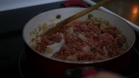 活泼的碎土耳其肉用在红色平底锅的葱在火炉-烤宽面条预习功课 股票视频