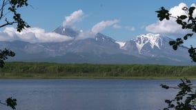 活火山,漂移横跨天空,登上的反射的云彩在高山湖 夏时流逝 股票视频
