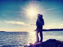 活跃人在从推挤诱饵的岩石海岸渔夫检查的海钓鱼 免版税库存图片