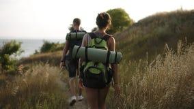 活跃休息概念,迁徙 年轻夫妇walkng通过小山的干燥植物 罕见的观点的yound男人和妇女 股票录像