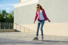 活跃在溜冰鞋的sportsl青少年的gir,都市背景 免版税图库摄影