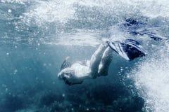 活跃妇女潜航的水中 免版税库存照片