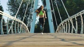 活跃妇女跑步的跑在城市人行桥在慢动作的后面视图 股票录像