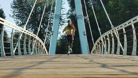 活跃妇女跑步的跑在城市人行桥在慢动作的后面视图 股票视频