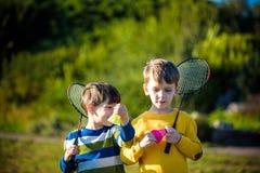 活跃学龄前打在室外法院的女孩和男孩羽毛球在夏天 孩子戏剧网球 孩子的学校体育 球拍 库存照片