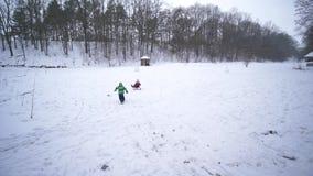 活跃寒假,精力充沛的儿童游戏并且跑与雪撬在多雪的森林里 影视素材