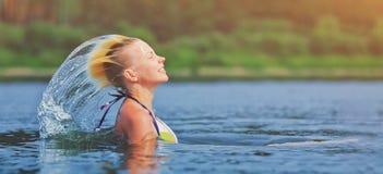 活跃年轻白肤金发的飞溅水的妇女挥动的头发在河 美丽的健康夫人放松和笑,抬头在外面 免版税图库摄影
