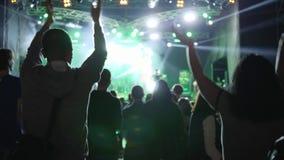 活跃爱好者用拍手和跳跃在摇滚乐音乐会的被举的手在夜 股票录像