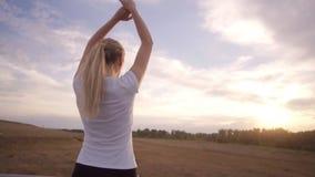 活跃生活方式和医疗保健 一个运动的女孩一件白色T恤杉的和有长的头发的停下来休息并且执行 股票视频