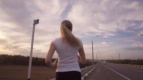 活跃生活方式和医疗保健 一个运动的女孩一件白色T恤杉的和有长的头发的沿一条几乎空的轨道跑 股票视频
