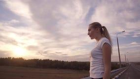 活跃生活方式和医疗保健 一个运动的女孩一件白色T恤杉的和有长的头发的站立面对落日 股票视频