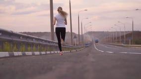 活跃生活方式和医疗保健 一件白色T恤杉和光运动鞋的一个运动的女孩沿一条空的轨道跑后边 股票录像