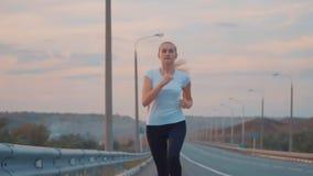 活跃生活方式和医疗保健 一件白色T恤杉和光运动鞋的一个运动的女孩沿一条空的轨道跑外面 影视素材