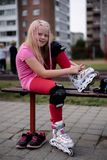 活跃生活方式在一个现代城市-女孩在体育场投入溜冰鞋 免版税库存照片