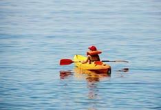 活跃男孩,获得乐趣享受冒险的经验划皮船在海 免版税图库摄影