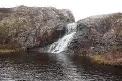 流入下来从岩石岸湖河 免版税库存照片