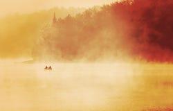 流出钓鱼在湖的渔夫,早期的有薄雾的有雾的早晨s 免版税库存图片