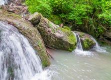 流动下来从岩石,小河合并入一个小池塘 库存照片