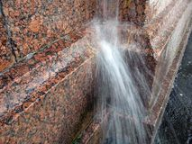 流动从在花岗岩墙壁上的水落管的水一架强的喷气机 库存图片