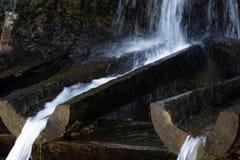 流动从自然山来源的纯净的矿物饮用水 库存照片
