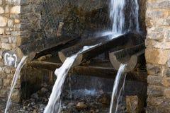流动从自然山来源的纯净的矿物饮用水 免版税图库摄影