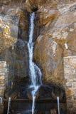 流动从自然山来源的纯净的矿物饮用水 免版税库存照片