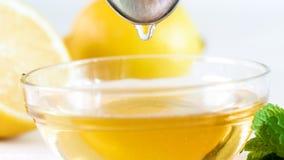 流动从金属匙子的蜂蜜的宏观图象在玻璃碗 免版税图库摄影