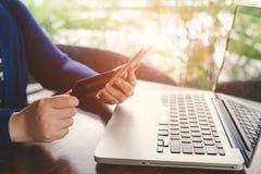 流动付款 使用智能手机和信用卡f的女性手 免版税图库摄影