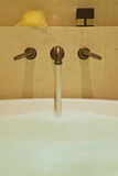 流动入白色浴缸的水从黄铜轻拍在墙壁登上了 图库摄影