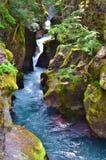 流动在一个岩石峡谷裂隙的水色蓝色河 免版税库存图片