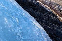 流动在一rockface下的冰川冰用熔化的水 免版税图库摄影