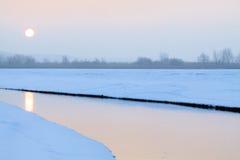 流动在冬天的小小河在日出期间 库存图片
