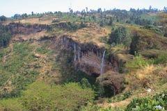 流动在岩石中的高和稀薄的Sipi秋天 免版税库存照片