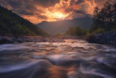 流动在日落时间的快速的山河 免版税图库摄影
