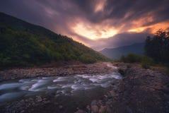 流动在日落时间的快速的山河 免版税库存图片