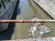 流动在河的污水和浮动垃圾在桥梁下 免版税库存图片