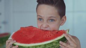流动在牙下的愉快男孩开胃吃红色西瓜和汁液 股票录像