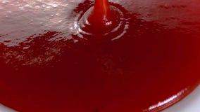 流动在白色板材上的蕃茄红色调味汁 从调味汁瓶的手倾吐的调味汁在白色板材上 库存图片
