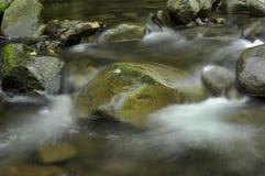 流动在石头之间的水 免版税库存照片