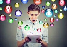 流动技术高科技概念 使用有社会媒介应用象的惊奇人片剂计算机飞行在屏幕外面 免版税库存图片