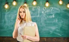 流动报告概念 有书的妇女谈话在手机在教室 被集中的面孔解决的老师 库存图片