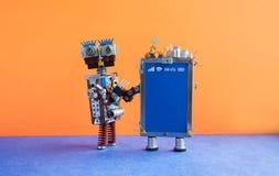 流动智能手机小配件机器人助理 滑稽的机器人玩具字符,创造性的设计触摸屏电话设备,光 库存图片