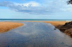 流动横跨海滩和出水口的溪入海 免版税库存照片