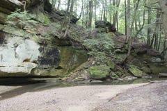流动由岩石墙壁的小河 免版税库存图片