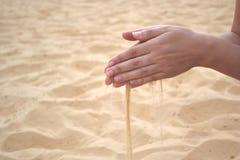 流动的沙子通过手指 免版税库存照片